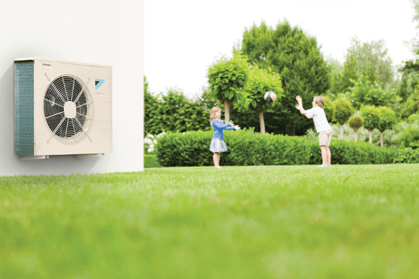 A Daikin Air Source Heat Pump With Kids Playing In The Background